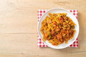 Fusilli pasta with ham and tomatoes sauce photo