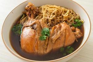 fideos con pollo a la brasa en sopa marrón foto