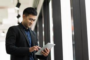 Young handsome asian businessman in suit using tablet in office. photo