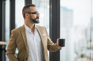 joven y guapo negocio bebiendo una taza de café foto