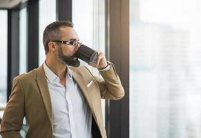 Young handsome business bearded man drinking cup photo