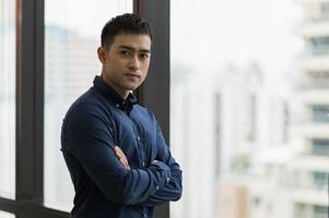 Young handsome asian businessman standing near window photo