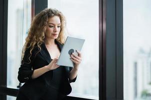 mujer de negocios hermosa joven que usa la tableta en la oficina. foto