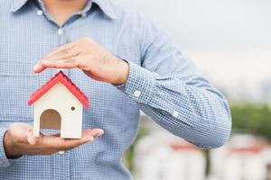 Hand holding mockup house. Real estate loan insurance photo