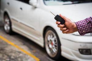 Hand holding car keys with car on background photo