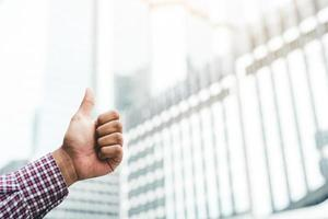 Close up businessman showing thumb ups on city background. photo
