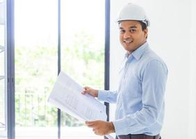 Young asian engineer or architects holding layout plan of building. photo