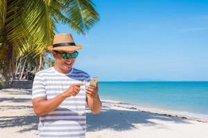 joven asiático en la playa con smartphone. foto
