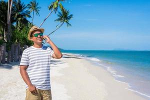 Young asian man on the beach using smartphone. photo