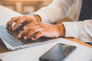 cerrar empresario usando en la computadora portátil para su trabajo. foto