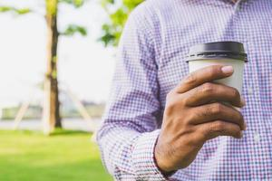 Close up hand man holding coffee paper cup. photo