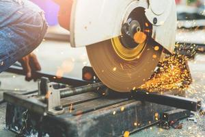 Close up worker using machine cutting steel photo