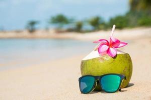 Coconut and sunglasses on tropical beach. photo