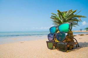 Pineapple with three sunglasses on tropical beach photo
