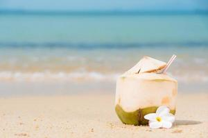Coconuts with drinking straw on the tropical beach. photo