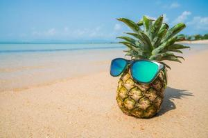 Pineapple with sunglasses on tropical beach background. Summer concept photo
