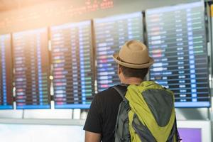 Traveler man looking at flight timetable in airport. photo