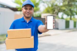 hombre de entrega azul que sostiene la caja de cartón del paquete y que muestra el teléfono inteligente. foto