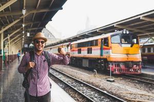 Young traveler man at platform train station. Traveling concept. photo