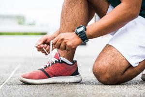 Runner young man tying shoelace getting ready for race on run track. photo