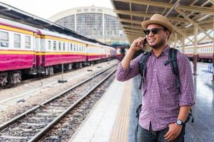 Young man Standing at train station and using smartphone photo