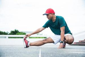 Young asian man stretching legs before run with copy space. photo