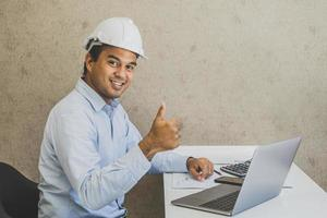 Asian civil engineer working planning project with laptop. photo