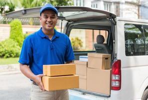 Deliver man in blue uniform and parcel cardboard box photo