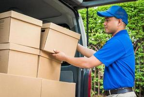 Blue delivery man pick up the parcel cardboard box in the truck photo