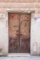Dañado antiguo edificio de hormigón y puerta de madera roja foto
