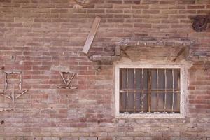 Antigua casa vintage de pared de ladrillo rojo y ventana rústica foto