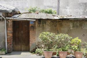 Damaged old concrete bungalow house building and red wood door photo