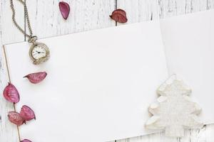 Paper with white Christmas tree, petals and a watch photo