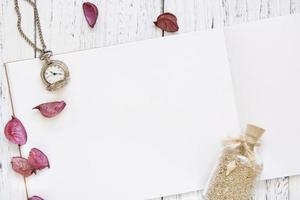 White wood table purple flower petals pocket clock glass sand bottle photo