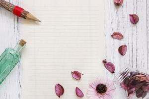 Paper with petals, pencil and bottle photo