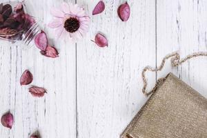 Purse and flower on white wood photo