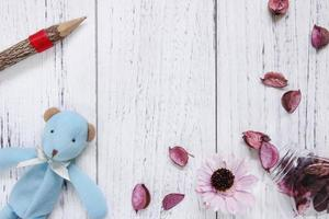 Toy with pencil and petals on white wood photo