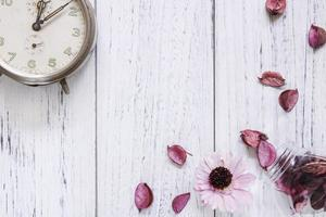 Petals and clock on white wood photo