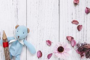 Pencil, toy and petals with white wood photo