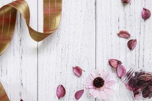 Petals and ribbon on white wood photo