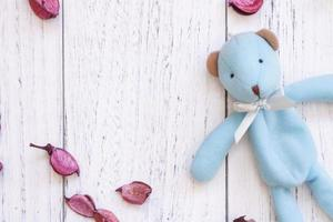 Bear and petals on white wood photo