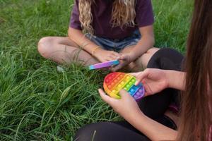 las niñas juegan al juguete popular pop-it con toque de silicona colorido foto