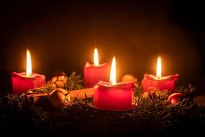 Decorated advent wreath made of fir branches with burning red candles photo