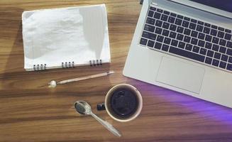 Escritorio de oficina de madera de vista superior con una taza de café portátil y un cuaderno foto