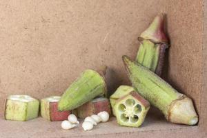 large and small size okras okras on wooden table photo