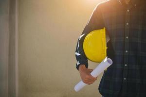 Close up Businessman holding yellow hard hat builder photo