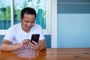 Hombre asiático vestido con camisa blanca usando el teléfono en una mesa de madera foto