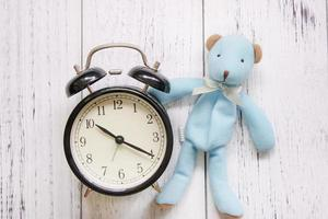 Bear and clock on white wood photo