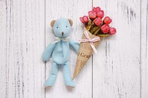 Bear and flowers on white wood photo
