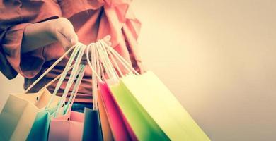 Primer plano de una mujer sosteniendo una bolsa de compras de papel de color foto